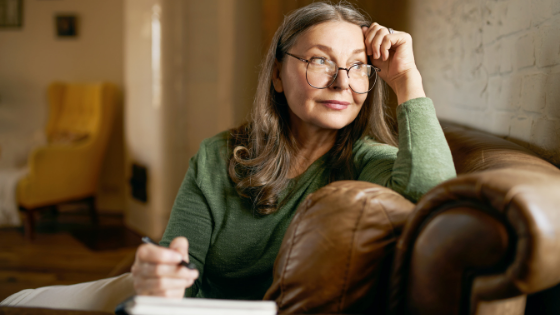 An older woman wearing glasses stares off as she makes a written list