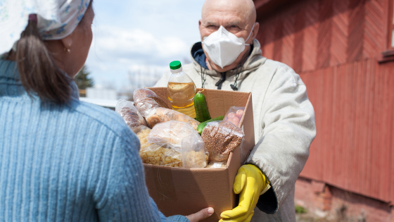 A senior man wearing a mask and gloves hands off a box of food items for the local food pantry