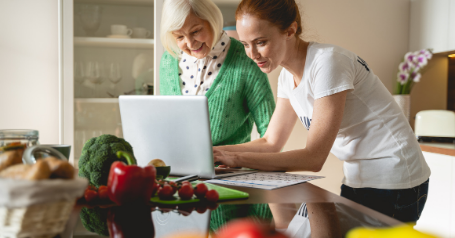 An older woman and a young woman are seen using a laptop to reference as they cook
