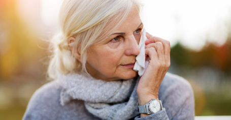 An older woman is seen wiping her tears while sitting on a park bench