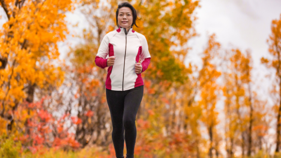 An older Asian woman is seen running in the woods in autumn