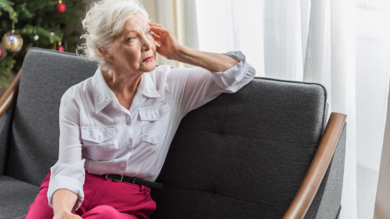 An older senior woman sitting on a couch looks upset out a window with a Christmas tree in the background
