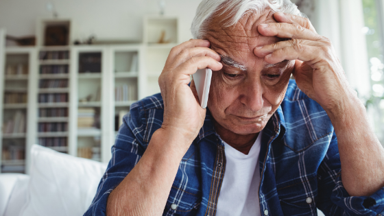 A senior man looks distraught while on the phone