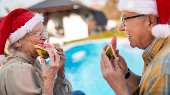 A senior couple wearing Santa hats snack on watermelon by the pool