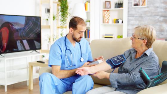 A male nurse checks a senior woman's blood pressure at home