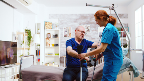 A female home health aide helps a senior man out of a hospital bed set up in his living room