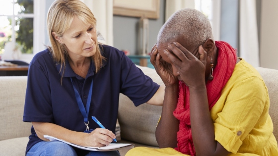 An in-home counselor comforts a distressed senior female client
