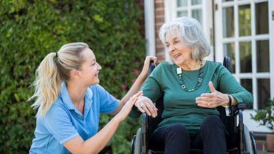 A senior woman in a wheelchair speaks with her home health aide outdoors