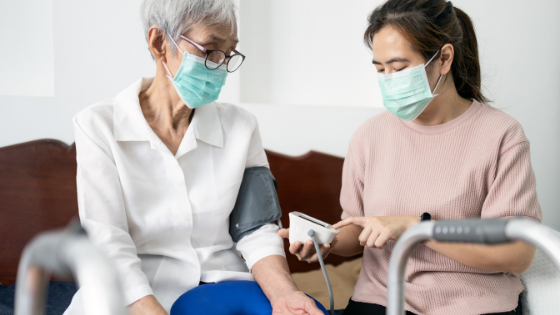 A senior woman wearing a mask is seen having her vitals checked by a home health aide also wearing a mask