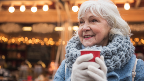 A senior woman wearing gloves and a scarf drinks a hot beverage outside