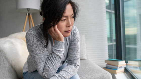 A sad looking Asian senior woman sits up on her couch