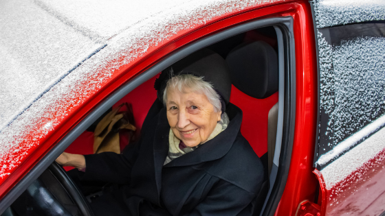 A senior woman smiles while sitting in her snow covered car
