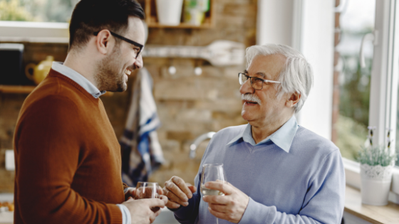 A senior man talks to a younger man while drinking wine