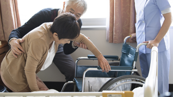 A senior man is seen helping his elderly wife into her wheelchair