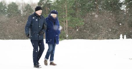 A senior couple bundled up walks through the snow