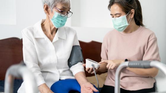 A woman wearing a mask checks a senior woman's blood pressure
