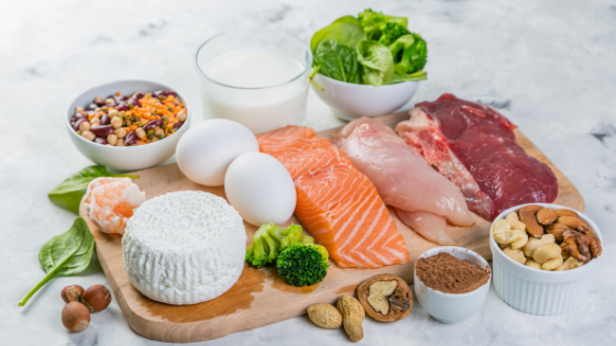 A cutting board with fresh low sodium proteins like fish, meat, lentils and more