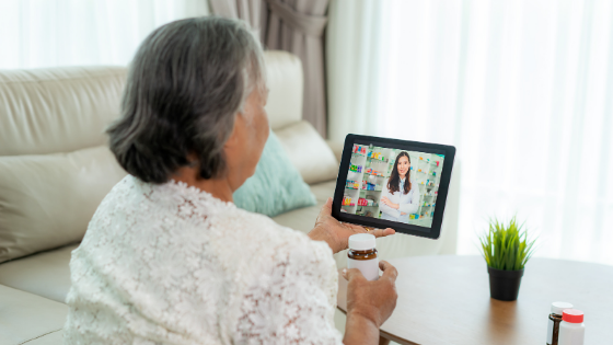 A senior woman holds up her prescription while on a video visit with her doctor