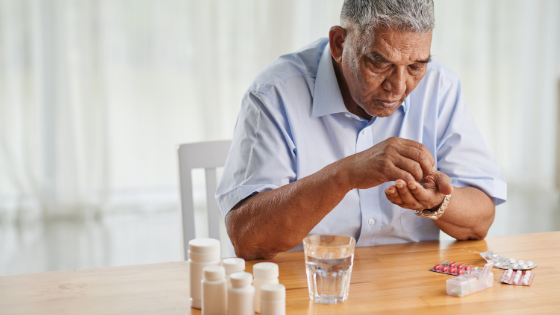 A senior man is seen counting out his pills