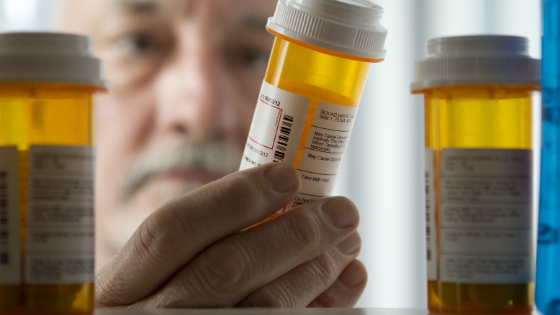 A senior man reaches into his medicine cabinet for his prescription
