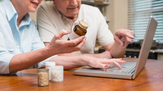 A senior couple track their prescriptions on the computer