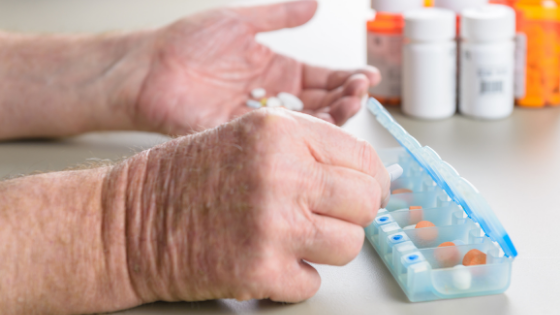 Close up of elderly hands organizing medications in a daily pill box