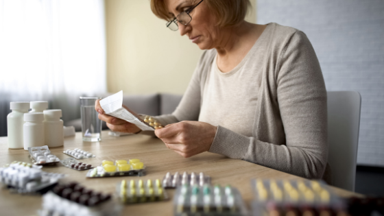 A senior woman carefully reads instructions for her medications