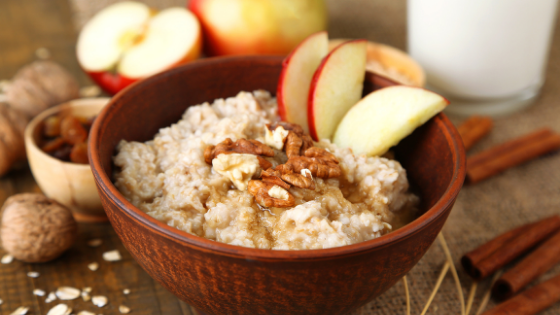 A bowl of oatmeal topped with apples, cinnamon & nuts