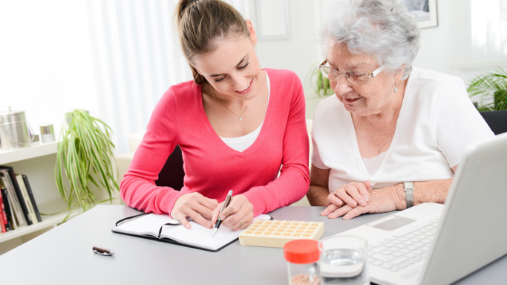 A young woman helps an elderly woman track and manage her medications