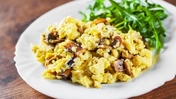 A plat of scrambled eggs with mushrooms and arugula