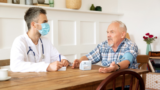 A doctor wearing a mask talks with a senior man in his home while taking his blood pressure