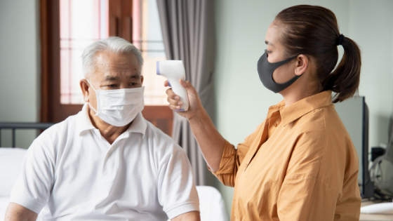 Senior man wearing mask getting temperature check