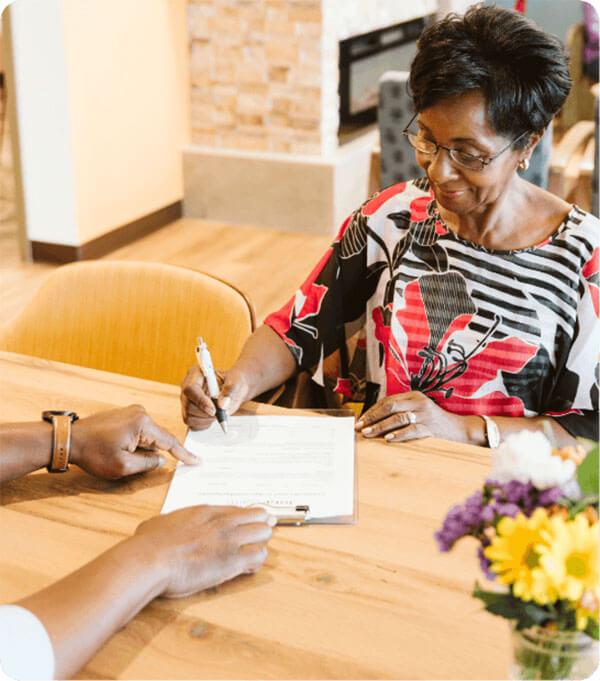 Mujer mayor que completa el formulario de admisión en la recepción.