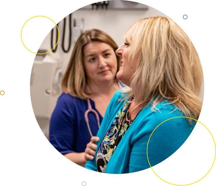 Nurse practitioner examining senior female patient in exam room