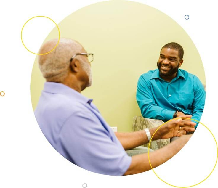 A senior male patient talks to his male Health Coach in reception area