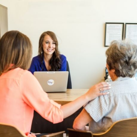 A caregiver supports a senior as they talk with an Iora Operations Assistant