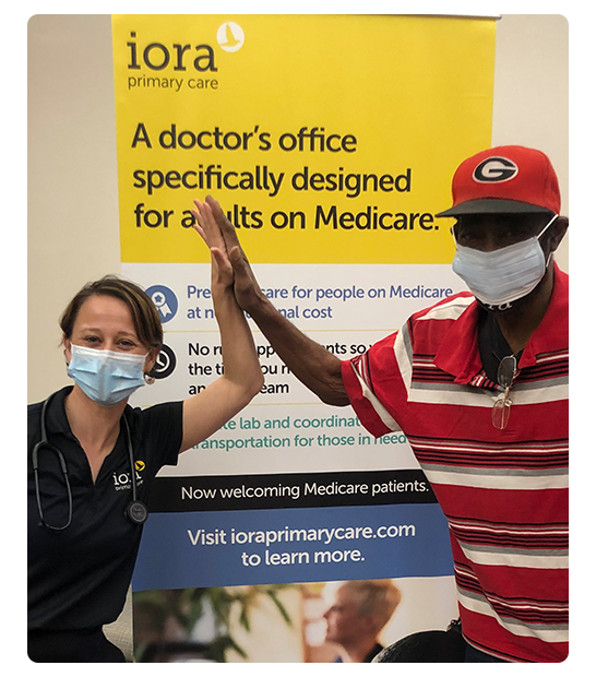 An Iora provider and patient high five while wearing masks
