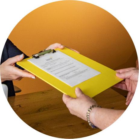 A receptionist handing a patient a clipboard