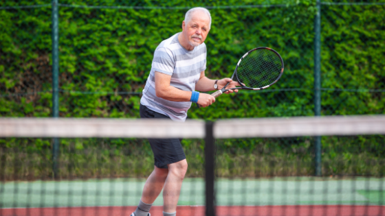 A senior man is seen playing tennis