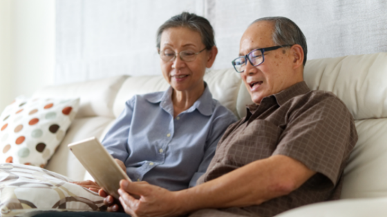 A senior couple watches a video on their tablet