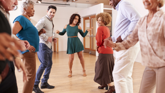 A group of seniors is seen taking dance lessons from an insturctor