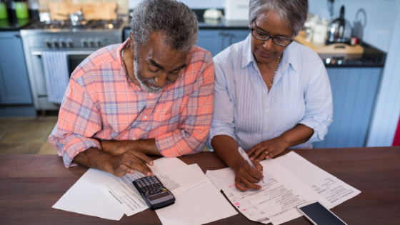 A senior couple calculates costs and paperwork