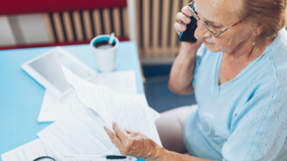 A senior woman looks at paperwork while on the phone
