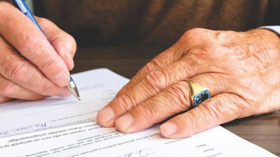 Close up of a man signing paperwork