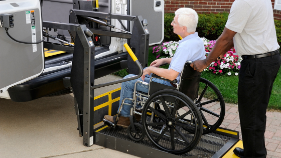 A senior man in a wheelchair is lighted into a handicap-accessible van