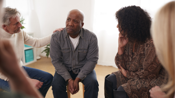 A senior man looks distraught during group therapy