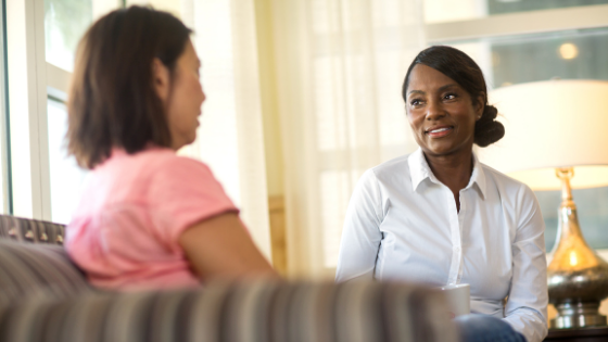 A Black senior woman having a conversation with another woman on a couch