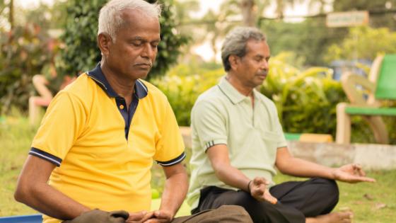 Two senior men practice mindful meditation outside