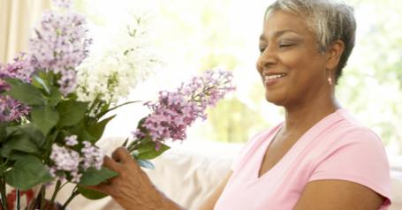 A senior woman smiles as she arranges a bouquet of fresh lilacs