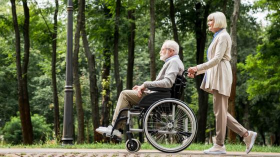 A senior man in a wheelchair and his wife take a stroll through a wooded trail